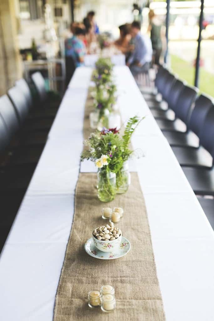 Rustic hessian table runner with beeswax candles and jam jar flowers